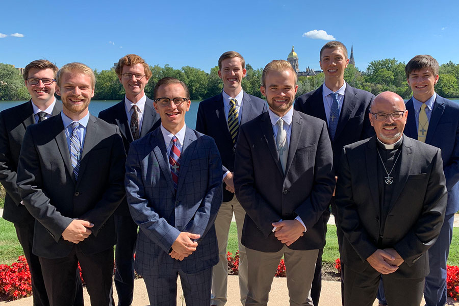 Mr. Ben Sasin '14, third from left in the front row, has answered God's call to become a priest. On the campus at Notre Dame, he stands with his cohort group that is pursuing a master's degree as part of each postulate's preparation for entering the priesthood.