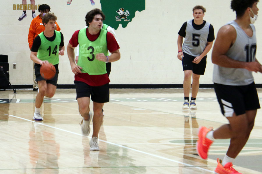 Senior Nathan McCahill (14) brings the ball up the court during the intramural basketball championship game on April 7 in the Welch Activity Center.
