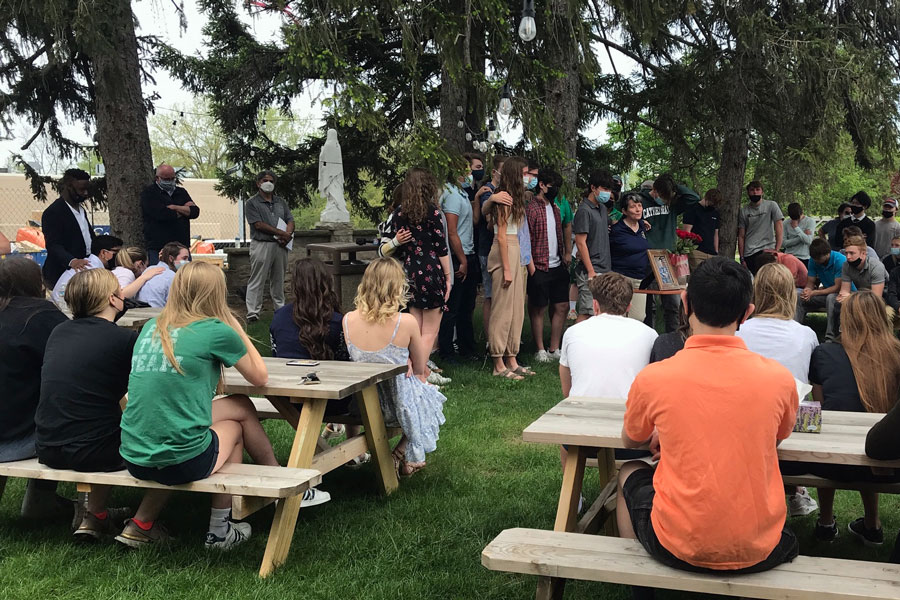 Surrounded by members of the speech and debate team, their coach, Mrs. Jeanne Malone, addresses the students who gathered on campus on May 2 to mourn the passing of junior Lendon Byram.