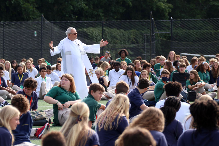 Fr.+Jeff+Godecker+walks+among+students+on+the+football+field+during+the+first+Mass+of+the+school+year.+Mass+also+will+be+celebrated+on+Sept.+15.+