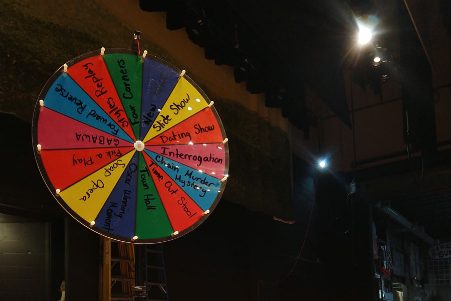 A+wheel+on+the+auditorium+stage+helps+the+improv+team+select+its+next+skit.+