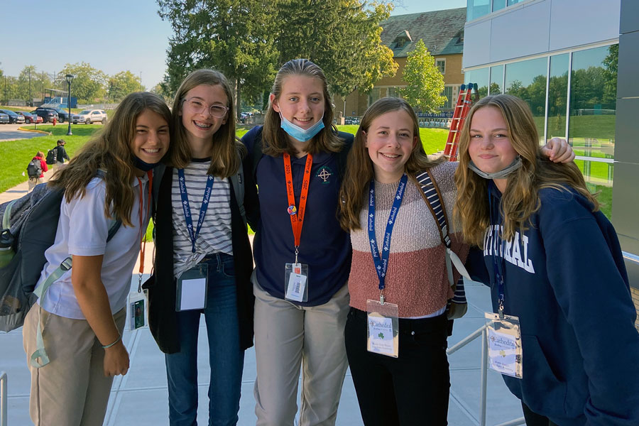 A group of eighth-graders and their host gather outside the Innovation Center at the end of their visit to campus.